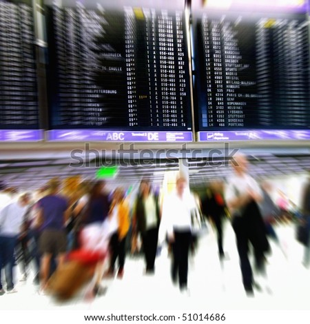 Airport passengers in a departure terminal in front of an schedule display - Motion Blur -