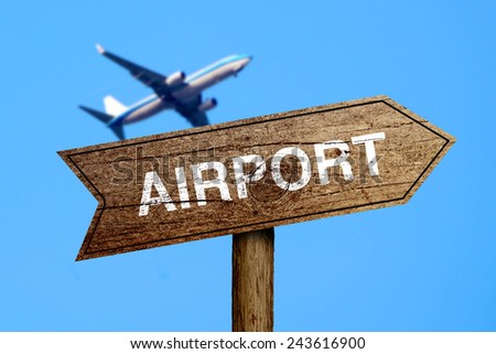 Airport road sign with the background of airplane flying in blue sky. - stock photo