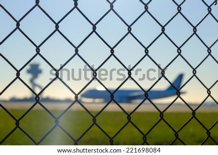 airport security fence with airliner and control tower out of focus - stock photo
