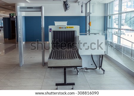 Airport security metal detector scan. Empty scanner control persons at the terminal.  Gate-ray detection with a belt for scanning luggage. Check point. - stock photo