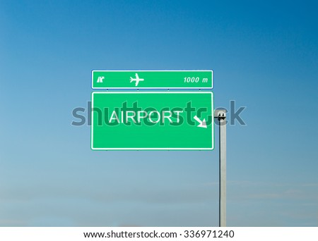 Airport sign on a highway with blue sky in the background - stock photo