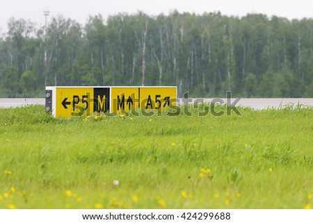 Airport sign pointer taxiways. Directional sign markings on the tarmac of runway at a commercial airport - stock photo