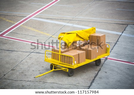 Airport vehicle transporting air cargo  to airplane on runway - stock photo