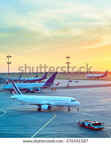Airport with many airplanes and beautiful sunset sky