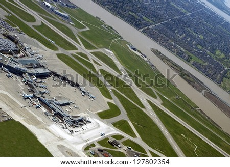 Airport with terminals, aircrafts and runways by the city and river - stock photo