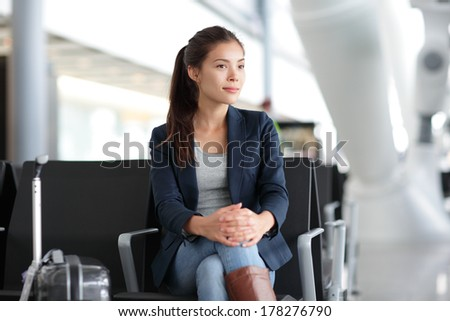 Airport woman waiting in terminal. Air travel concept with young casual business woman sitting with carry-on hand luggage trolley in airport lounge. Beautiful young mixed race female professional - stock photo