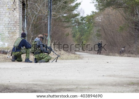 Airsoft players holding position in ruins - stock photo