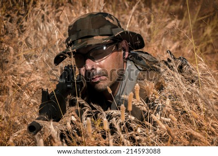Airsoft team member in daytime action hiding in the bushes. - stock photo