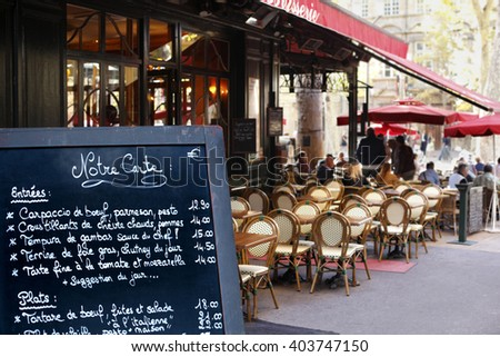 Aix en Provence, France - September 14, 2010: French bistro restaurant menu board with customer seating area in the background