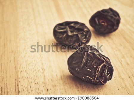 Ajwa Dates fruit on wooden table in retro style (Ajwa is a soft dry variety of date fruit from Saudi Arabia. It is cultivated at the city of Madinah) - stock photo