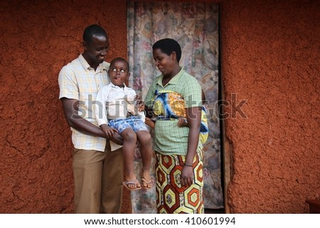 AKAGERA, RWANDA - CIRCA OCTOBER 2015: a Rwandan family lives comfortably in a village house bordering the Akagera national park. Both husband and wife are imigongo artists using art for empowerment.