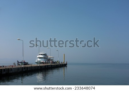AKCAY, TURKEY - AUGUST 15, 2014: Concrete pier with some people spend misty morning in a coastal town called Akcay in Turkey. - stock photo