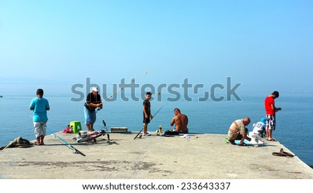 AKCAY, TURKEY  - AUGUST 15, 2014: Group of fishing enthusiasts angle on pier early morning in Akcay, Turkey