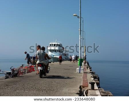 AKCAY, TURKEY - AUGUST 15, 2014: People spend misty morning on a concrete pier in Akcay, Turkey - stock photo