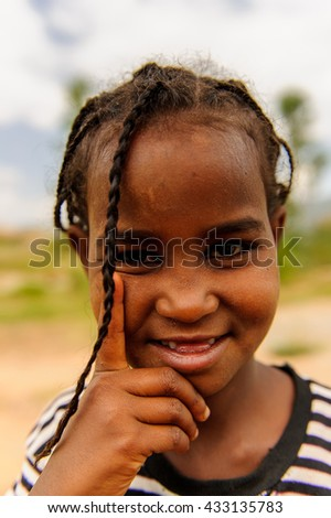 AKSUM, ETHIOPIA - SEP 24, 2011: Unidentified Ethiopian beautiful girl with pigtails smiles for camera in Ethiopia, Sep.24, 2011. People in Ethiopia suffer of poverty due to the unstable situation
