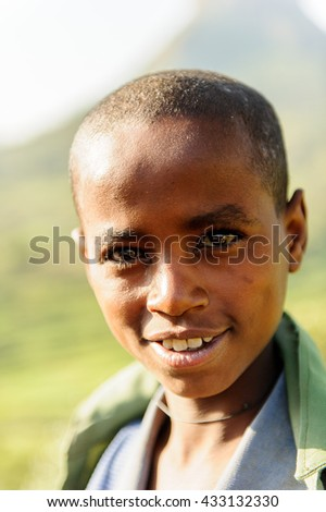 AKSUM, ETHIOPIA - SEP 25, 2011: Unidentified Ethiopian cute little girl in green tissue near the stone wall in Ethiopia. Children in Ethiopia suffer of poverty due to the unstable situation
