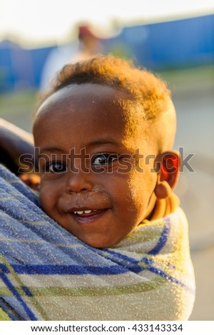 AKSUM, ETHIOPIA - SEP 30, 2011: Unidentified Ethiopian little cute happy boy is carried on his mother back in Ethiopia. Children in Ethiopia suffer of poverty due to the unstable situation - stock photo
