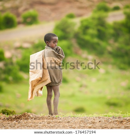 AKSUM, ETHIOPIA - SEPTEMBER 22, 2011: Unidentified Ethiopian boy walks with old bag with the green nature background. People in Ethiopia suffer of poverty due to the unstable situation - stock photo