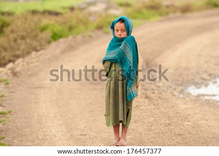 AKSUM, ETHIOPIA - SEPTEMBER 22, 2011: Unidentified Ethiopian girl walks over the road. People in Ethiopia suffer of poverty due to the unstable situation