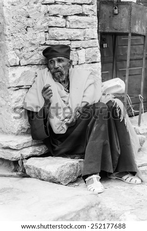 AKSUM, ETHIOPIA - SEPTEMBER 24, 2011: Unidentified Ethiopian man in traditional clothes sit at the porch of the house. People in Ethiopia suffer of poverty due to the unstable situation
