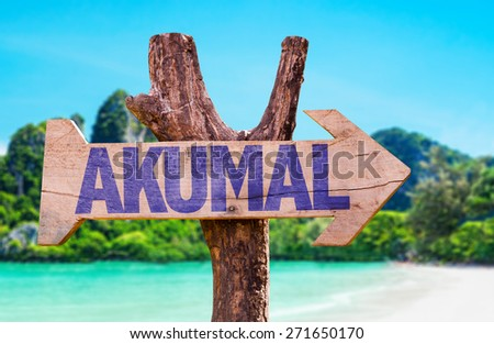 Akumal wooden sign with beach background - stock photo