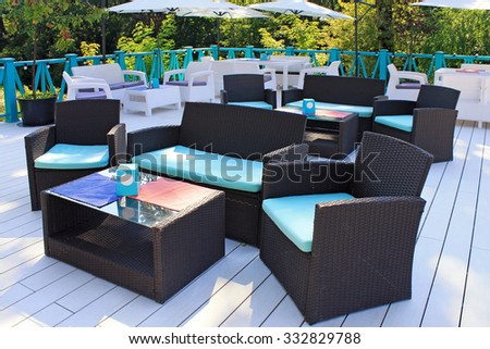 Al fresco cafe with rattan wicker armchairs and tables on the summer garden terrace - stock photo