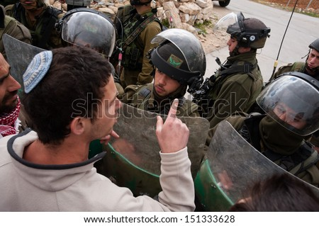 AL MA'SARA, PALESTINIAN TERRITORY - APRIL 5: A Jewish Israeli activist confronts Israeli soldiers in a protest against the separation wall in Al Ma'sara, West Bank, April 5, 2013. - stock photo