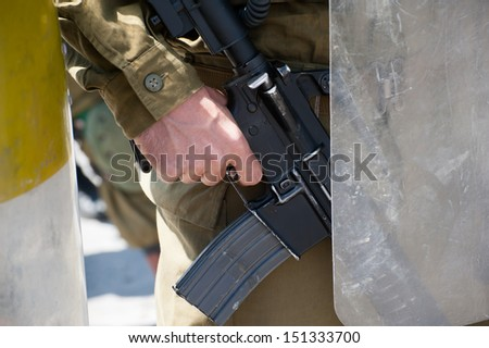 AL MA'SARA, PALESTINIAN TERRITORY - APRIL 12: An Israeli soldier's finger on the trigger of his assault rifle during a protest against the separation wall Al Ma'sara, West Bank, April 12, 2013.  - stock photo