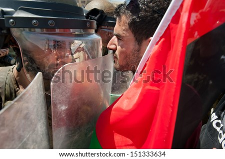 AL MA'SARA, PALESTINIAN TERRITORY - JUNE 7: Palestinian activists confront Israeli soldiers during a protest against the occupation and separation wall in the West Bank town Al Ma'sara, June 7, 2013. - stock photo