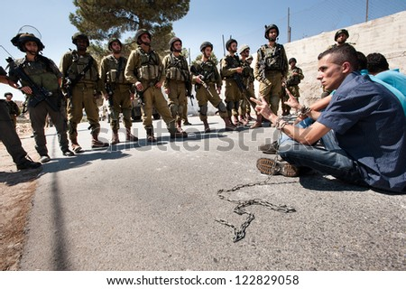 AL MA'SARA, PALESTINIAN TERRITORY - SEPTEMBER 14: Palestinians in chains symbolizing solidarity with prisoners in Israeli jails face soldiers during a protest in Al Ma'sara, West Bank, Sept. 14, 2012. - stock photo