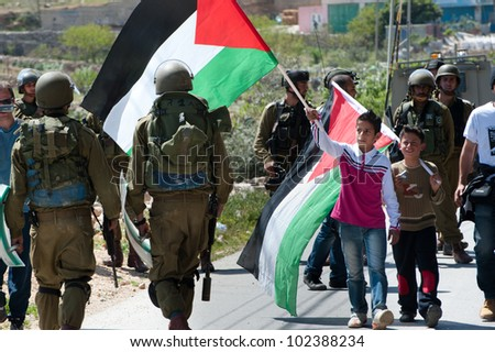 AL-MASARA, PALESTINIAN TERRITORIES - APRIL 6: A Palestinian boy waves his flag in the face Israeli soldiers during a protest against the separation barrier in Al-Masara, West Bank, April 6, 2012. - stock photo