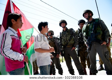 AL-MASARA, PALESTINIAN TERRITORIES - APRIL 6: Palestinian boys confront Israeli soldiers in a protest against the separation barrier in the West Bank town of Al-Masara, April 6, 2012.