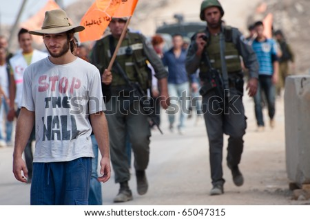 """AL-WALAJA, - NOVEMBER 13: An Israeli activist in a """"Stop the Wall"""" shirt marches on Nov. 13, 2010 to protest the Israeli separation wall in Al-Walaja. - stock photo"""