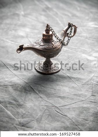 Aladdin Lamp on grey textile - stock photo
