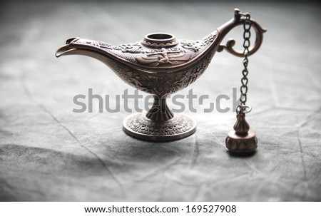 Aladdin Lamp on grey textile - stock photo