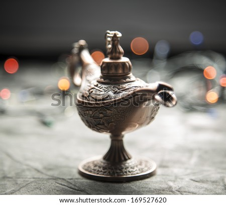 Aladdin Lamp on grey textile in front of bokeh lights