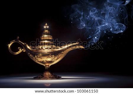 aladdin magic lamp on black with smoke - stock photo
