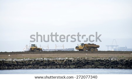 ALAMEDA, CA - APRIL 22, 2015: Clean up continues on the prior Navy Industrial Waste Dump located on the North West Corner of Alameda Point.  Tractors can be seen dumping and spreading new dirt. - stock photo