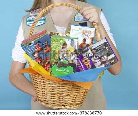 ALAMEDA, CA - FEBRUARY 18, 2016: Cadette Girl Scout holding Gift Basket with assortment of  ABC Baker's brand Girl Scout cookie boxes. Close up on basket in hands. Blue background - stock photo