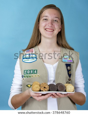 ALAMEDA, CA - FEBRUARY 18, 2016: Cadette Girl Scout Meaghan Fitzgerald holding a white rectangular plate with the five most popular original Girl Scout cookies created by ABC Bakers.  - stock photo