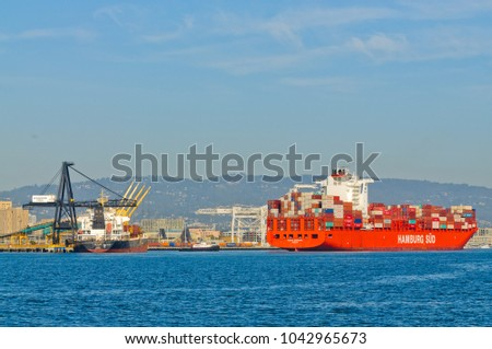"Alameda, CA - March 9, 2015: Oakland Oakland Container Shipyard, San Francisco Bay, the Hamburg Sud ship ""Santa Barbara"" entering harbor, maeuvering into dock"