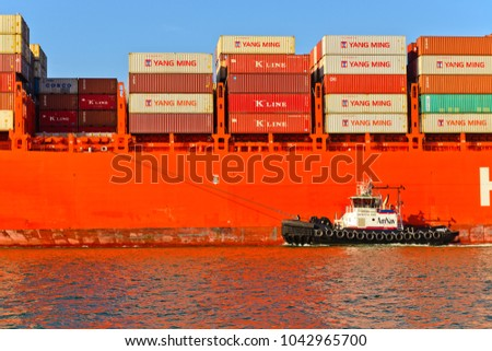 "Alameda, CA - March 9, 2015: Oakland Oakland Container Shipyard, San Francisco Bay, the Hamburg Sud ship ""Santa Barbara"" entering harbor, maneuvering into dock with the help of tug"