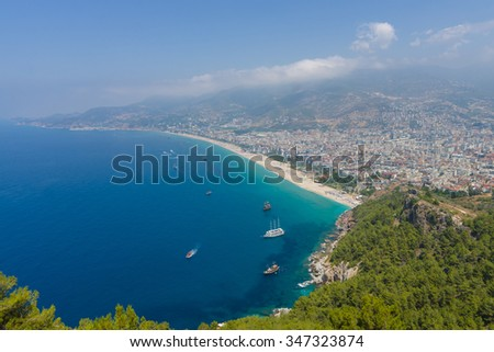 ALANYA, TURKEY - JULY 09, 2015: The city beach in Alanya. The coastline is receding into the distance. The view from the bird's eye view. Alanya - a popular holiday destination for European tourists.