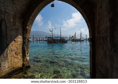 ALANYA, TURKEY - JULY 04, 2015: Traditional entertainment resort of Alanya. Sailing aka pirate ships around the fortress of Alanya. View from the medieval shipyard (Tersane) of the Alanya Castle.