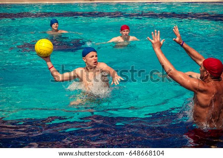Alanya, Turkey - May, 3, 2017: A group of people playing in the pool in a water polo ball. Athletes in blue and red hats, yellow ball. These people tourists came to rest on vacation.