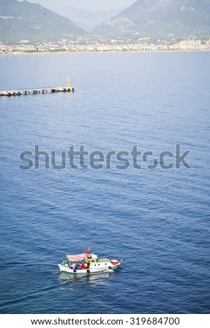 ALANYA, TURKEY - MAY 21, 2013: Tourist boat. The view from the mountain in Alanya city and the sea where swims the tourist boat, Alanya, Turkey