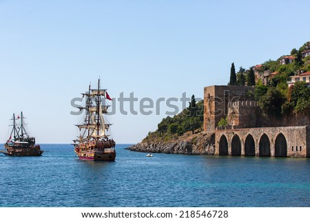 ALANYA -TURKEY - SEPTEMBER 10: pirate ship on the water of Mediteranean sea,  near the  Ruins of Ottoman fortress on 10 September 2013. Ship traveling around Alanya castle  - stock photo