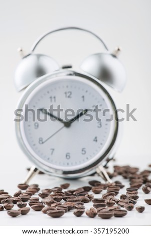 Alarm and coffee. Average alarm clock and coffee beans spread on white surface - stock photo