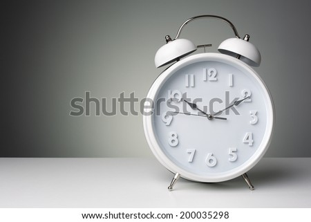 Alarm clock against a gray background with copy space - stock photo