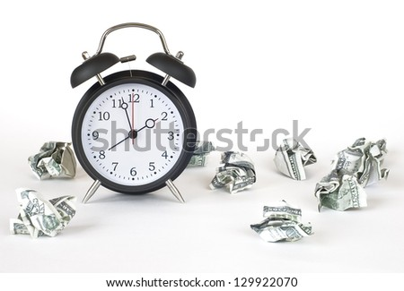 alarm clock and a crumpled dollar bills on a white background